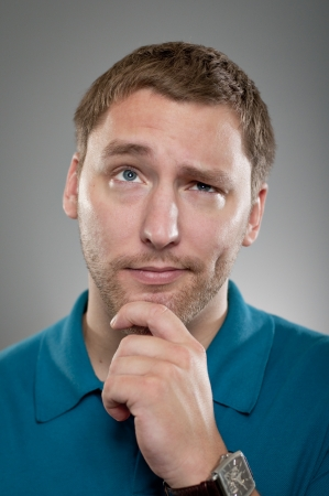 questioning: A Caucasian man in his 20s with his hand on his chin making a decision. Stock Photo