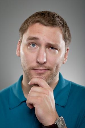 questionnement: Un homme de race blanche dans ses ann�es 20 avec sa main sur son menton de prendre une d�cision. Banque d'images