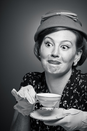 A woman in retro garb drinking a cup of tea.