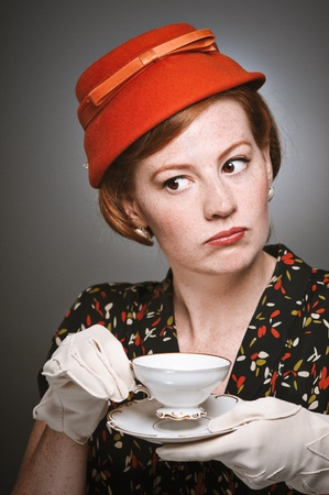 A woman in retro garb drinking a cup of tea. Stock Photo - 19313687