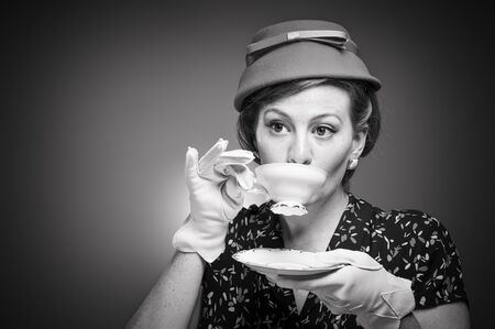 20 s: A woman in retro garb drinking a cup of tea.