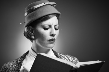 A woman in retro garb reading a book.