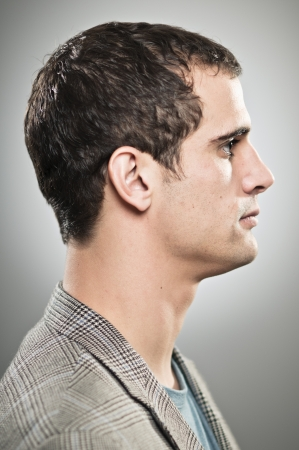 A caucasian man in his 20's with a blank expression in profile. photo