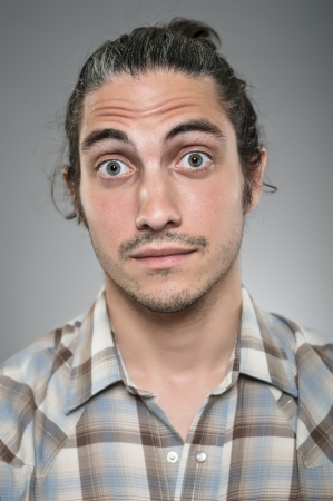 A Caucasian man in his 30s with a look of wide eyed surprise.