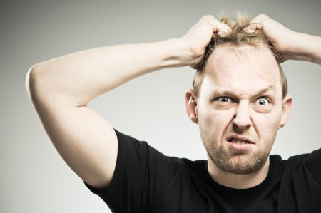 raised eyebrows: A Caucasian man in his 20s pulling out his hair and making a face.