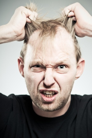 A Caucasian man in his 20s pulling out his hair and making a face. photo