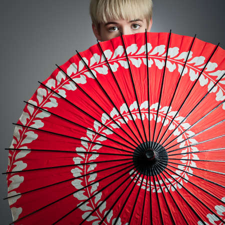 A short haired girl peeking over her red parasol.