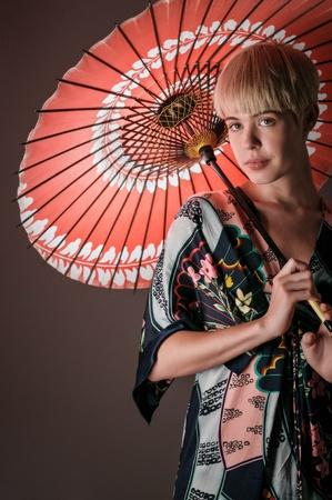 A cute girl portrait wearing a kimono dress and holding a parasol. Stock fotó