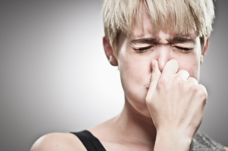 A beautiful young Caucasian woman in her twenties plugging her nose to hold her breath. Stok Fotoğraf