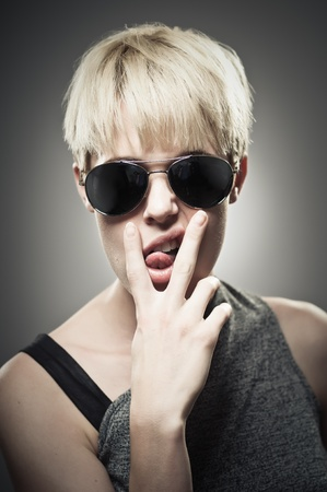 A beautiful young Caucasian woman in her twenties wearing aviator sunglasses and making a rude hand gesture.