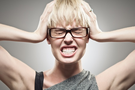 A beautiful young Caucasian woman in her twenties under stress pressure holding her head. photo
