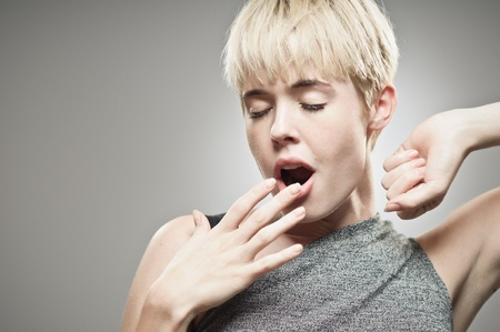 A beautiful young Caucasian woman in her twenties covering her mouth as she yawns.