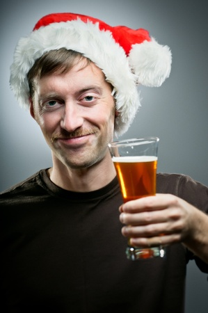 A Caucasian man wearing a Santa hat reluctantly toasts with a pint of beer.