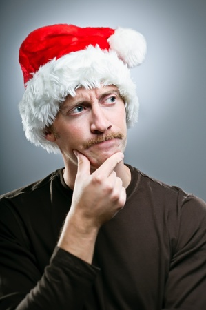 A Caucasian man wearing a Santa Hat deciding on what gifts to give for Christmas.