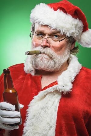 A bad Santa smoking a cigar and drinking beer. Stock Photo
