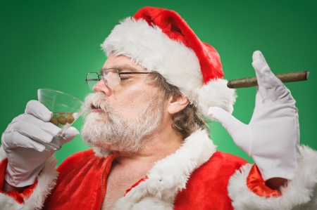 A bad Santa smoking a cigar and drinking a martini. photo