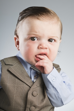 worried businessman: A 7 month old baby dressed in a suit. Stock Photo