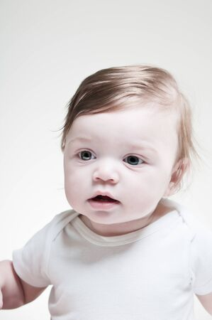 A studio portrait of a six month old baby. photo