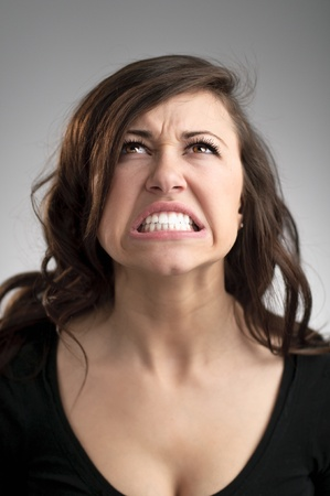 gritting: An angry young Caucasian woman portrait. Stock Photo