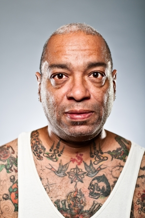 An African American man with style and many tattoos.