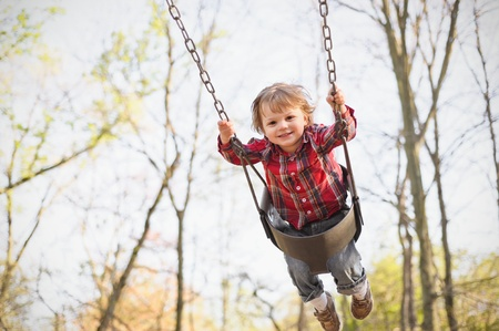A young toddler boy swinging in the fall. photo
