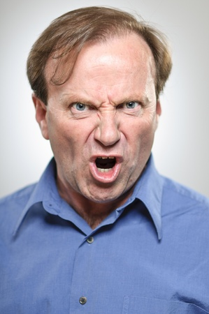 A mature man in his 50s furiously yelling with anger.