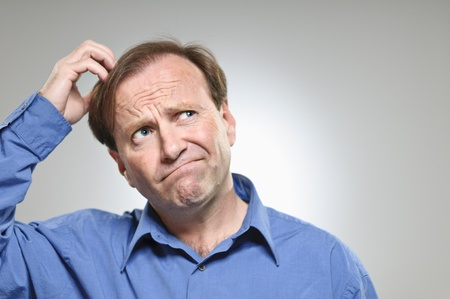 A mature man in his 50s scratching his head while making a decision.