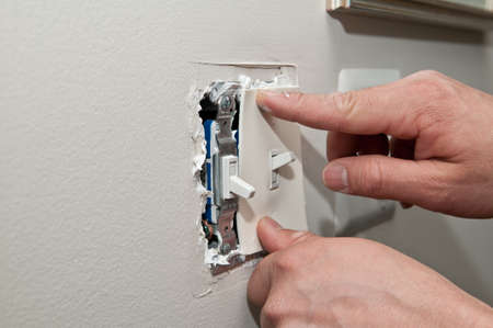 A worker installs insulation for light switches