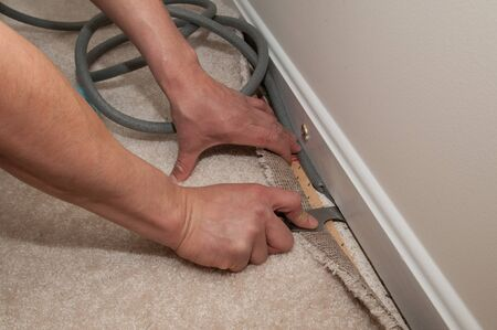 carpet: A man pulls back carpet in order to install insulation under the molding  Stock Photo