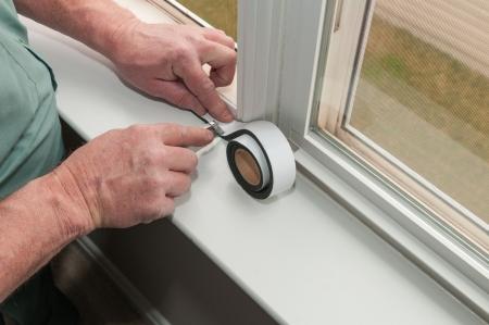 window frame: A worker installs insulation in window