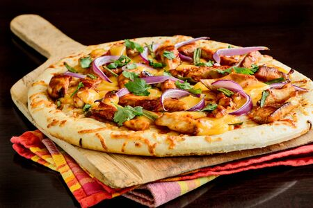 directly above: Gourmet pizza with barbeque sauce, grilled chicken, red onions, cheese and cilantro Stock Photo
