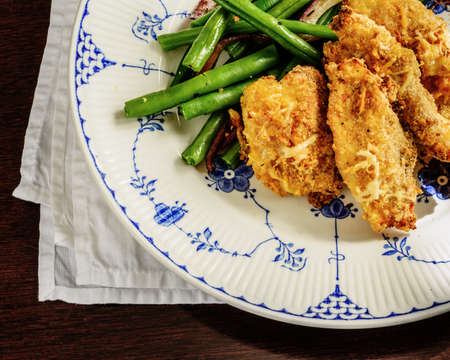 Breaded and baked chicken dinner with green beans.
