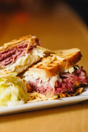 meat counter: Corned beef and pastrami sandwich with swiss cheese and sauerkraut with a side of potato sticks and clear pickle slaw. Stock Photo