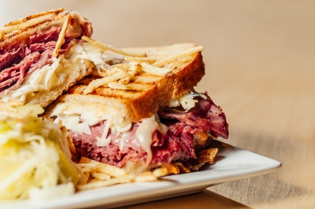 Corned beef and pastrami sandwich with swiss cheese and sauerkraut with a side of potato sticks and clear pickle slaw. photo