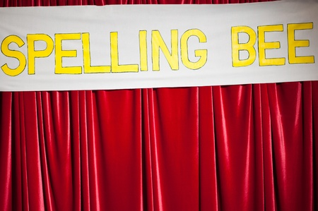 A spelling bee banner on a red curtain