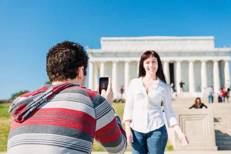 A tourist couple taking pics in front of the Lincoln Memorial