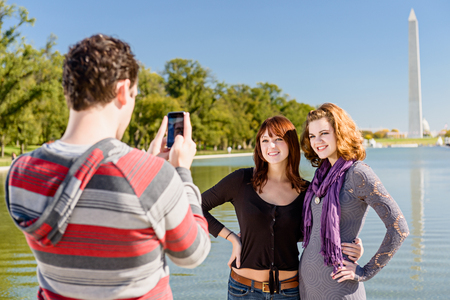 Tourists taking pictures in front of the reflecting pool in Washington DC  Stok Fotoğraf