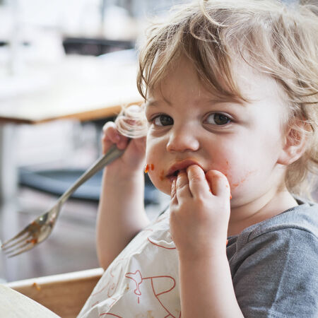 Toddler boy eating pasta