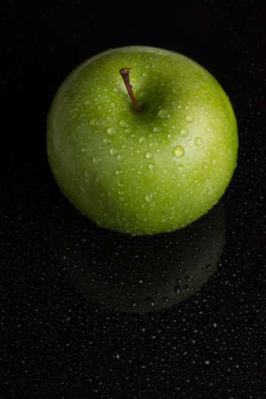 Green apple over the black Stock Photo - 16813905
