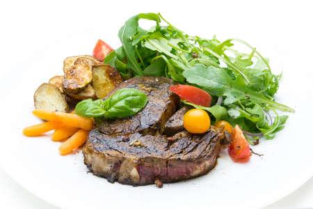 fine dining: Steak with arugula, tomato, potato and carrot Stock Photo