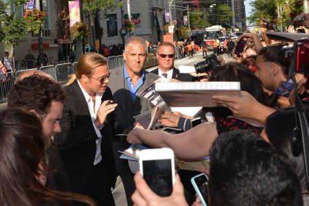 TORONTO - SEPTEMBER 6: Brad Pitt signs autographs for fans at the Toronto International Film Festival for his new film 12 Years a Slave on September 6, 2013.
