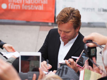 autograph: TORONTO - SEPTEMBER 9: Actor Ewan McGregor signs autograph for fans at the Toronto International Film Festival for his new film August: Osage County on September 9, 2013. Editorial