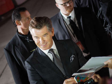 durchstechen: TORONTO - 12. SEPTEMBER: Schauspieler Pierce Brosnan unterzeichnet Autogramm f�r die Fans auf dem Toronto International Film Festival f�r seinen neuen Film The Love Punch on 12. September 2013.