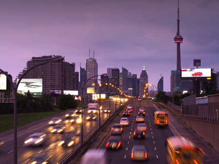 expressway: Toronto skyline at evening rush hour  Building signs removed  Stock Photo