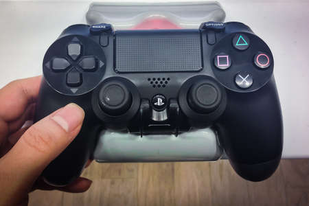 TORONTO - NOVEMBER 15: Customer holds an Playstaion 4 controller at the store in Toronto, Canada on November 15, 2013.