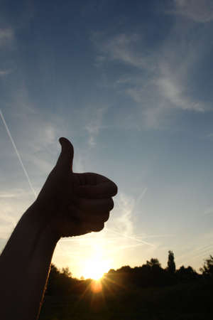 Thumbs up silhouette against a beautiful sunset