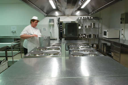 Chef cooking in a professional industrial kitchen Stock Photo