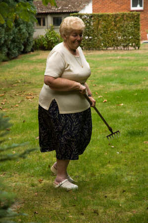 Senior woman with a passion for gardening working in her lovely garden photo