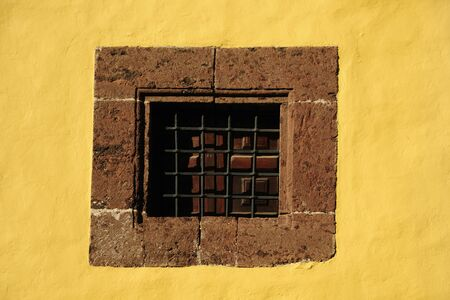 old window on yellow wall