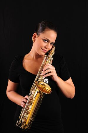 Young woman with saxophone on black background photo